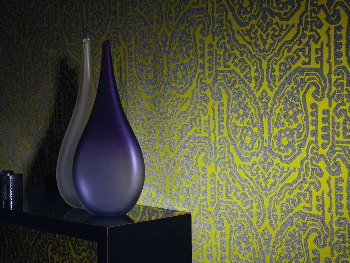 schwarze Konsole mit zwei tränenförmigen Vasen in den Farben elfenbein und violette und im Hintergrund eine Kiwigrüne Tapete mit Glitzerornamenten