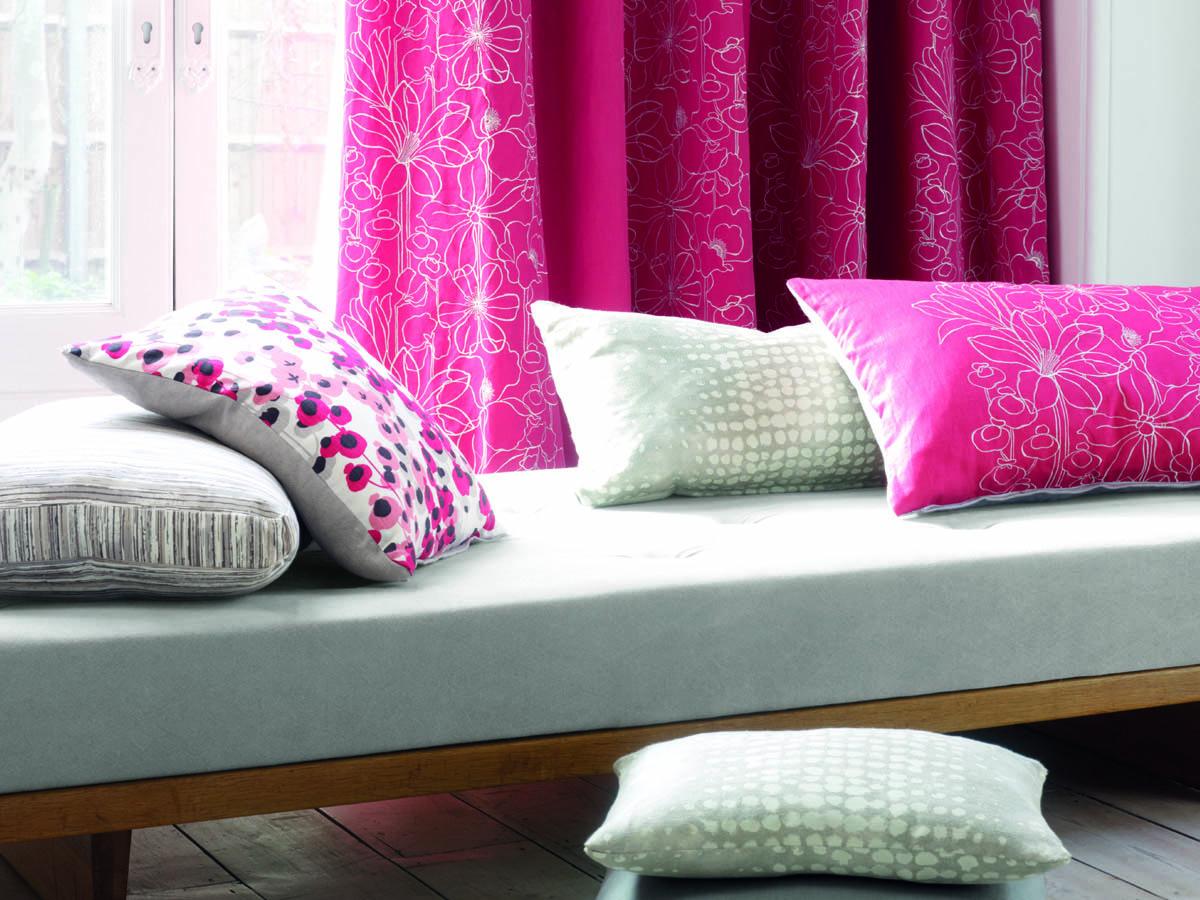 Das Bild zeigt im Hintergrund einen pinkfarbenen Vorhang als Sichtschutz. Davor befindet sich eine grau gepolsterte Sitzbank mit einem Holzgestell und zahlreichen Kissen in verschiedenen Farben und Größen.