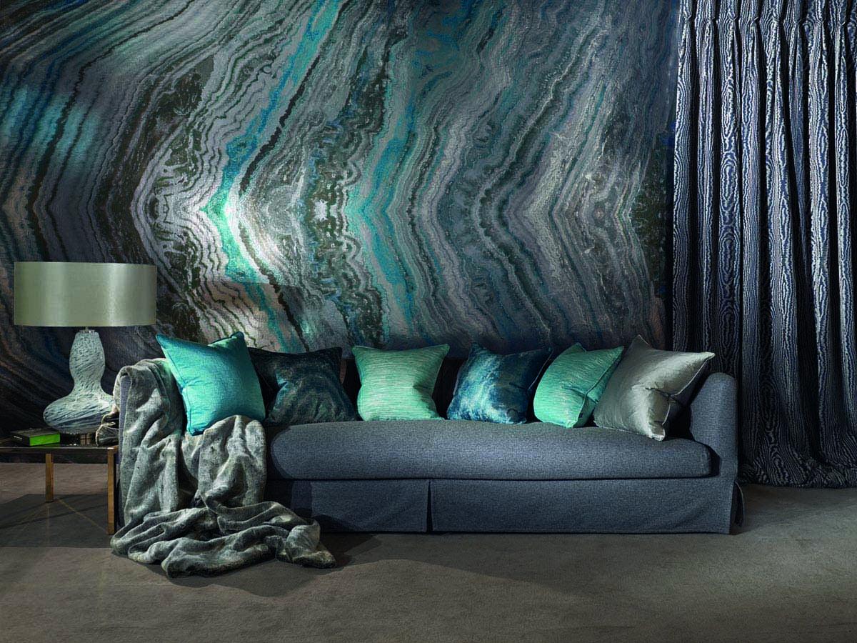 Bild eines Wohnzimmers mit Marmortapete in Metalloptik, Couch mit dunkelgrauem Stoffbezug, fünf Kissen in Metallfarben, eine glänzende Kuscheldecke, goldener Beistelltisch, Tischleuchte und einem Vorhang in Leopardenoptik.