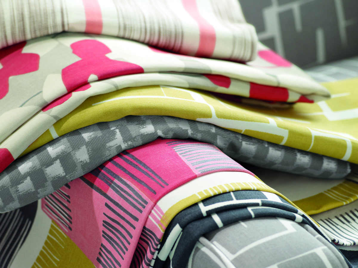 Bild mit Stoffen für Verdunklungsvorhängen in verschiedenen Dessins Streifen, Kästchen oder Blumen und in sommerlichen hellen Farben kiwigrün, rot, grau, weiß, schwarz und rosa