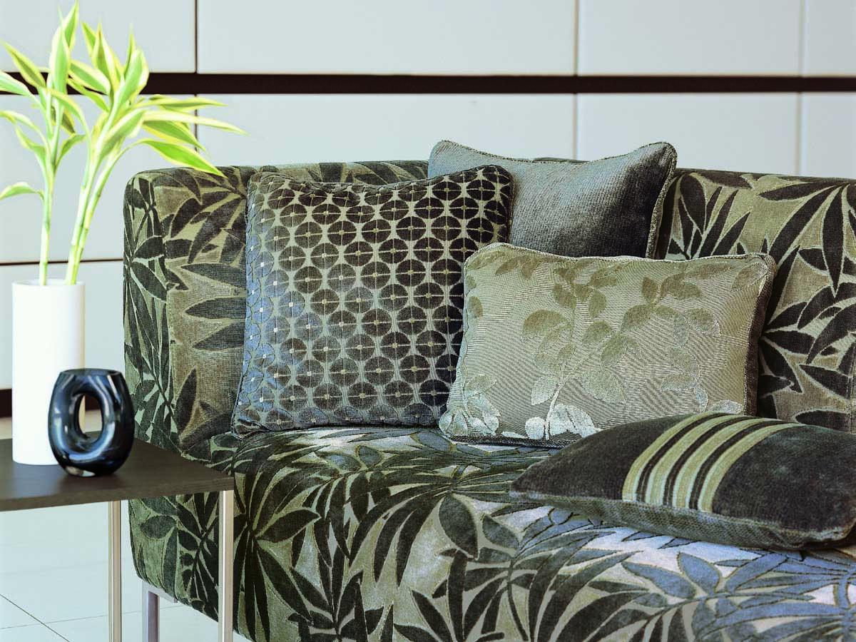 Couch mit floralen in Grün- und Erdtönen gehaltenen Samtbezug, dazu passende Kissen in verschiedenen Formen und Mustern, eine Dekovase in weiß, ein Beistelltisch mit einer Holzplatte und Füßen aus Metall