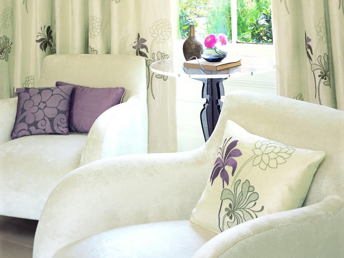 Lesebereich mit zwei Sesseln mit weißem Samtbezug und dekorativen Kissen in lila und weiß mit verschiedenen Mustern, hoher Beistelltisch aus Glas mit Dekoartikeln und Vorhänge mit Blumenmotiven in den Farben perlweiß und pflaume.