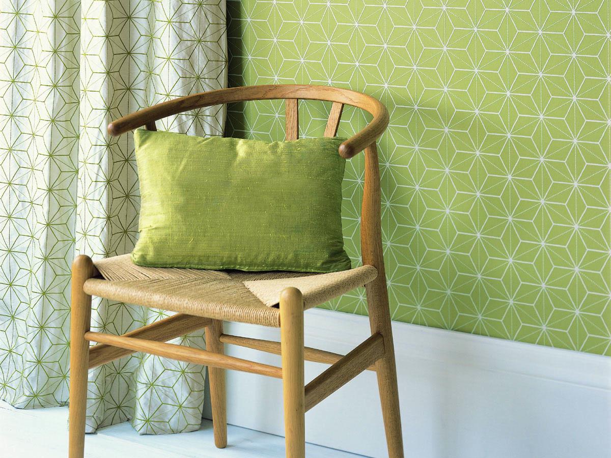 Echtholzstuhl aus Eiche kombiniert mit einem Dekokissen, Vorhang und Tapete in kiwigrün.