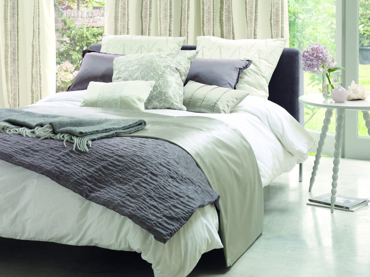 Freistehendes Bett mit Dekokissen und -decken in verschiedenen Erdtönen, filigranen weißen Beistelltisch, beigefarbigen Vorhängen und wohnlichen Dekoartikeln.